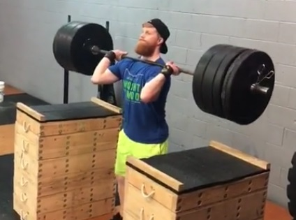 An athlete with the barbell in rack position (on the shoulders) after lifting it from the jerk blocks