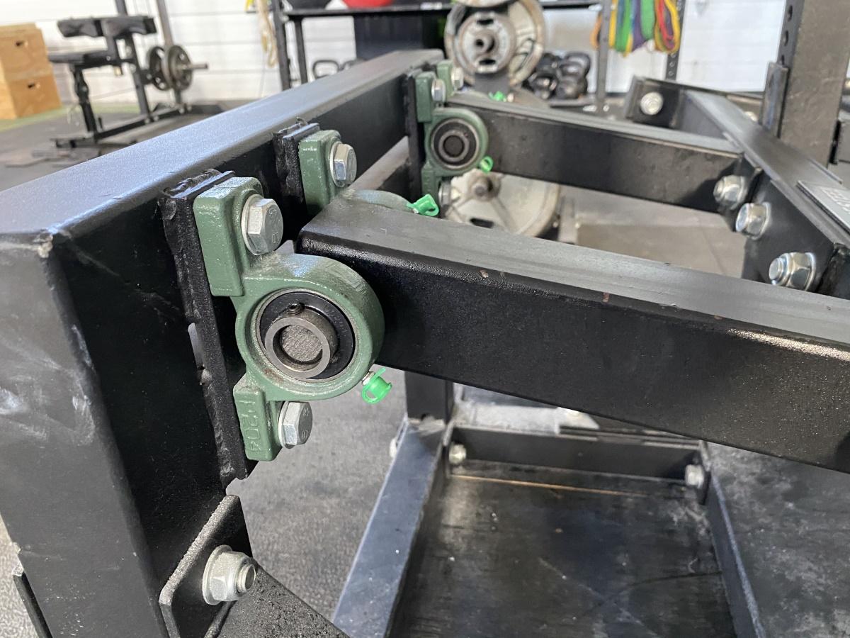 Bushings on belt squat machine