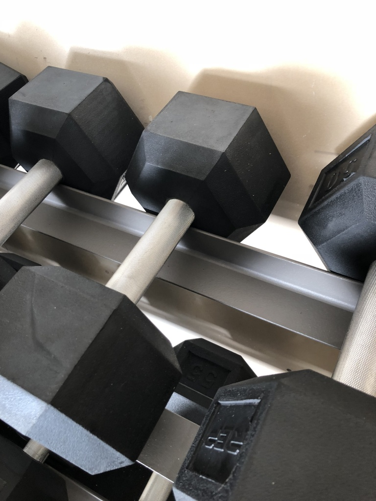Rep rubber hexagon dumbbell set on XMark rack